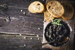 Schwarzer russischer gesalzener Störkaviar Astrakhans in einer Dose auf dunklem Hintergrund mit hölzernem Löffel und Scheiben bro Stockfoto