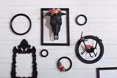 Schwarzer Schädel eines Rotwilds und der Hörner auf einer hölzernen weißen Wand mit leeren Rahmen für Malereien Das Konzept der V lizenzfreies stockbild