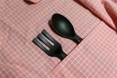 Schwarzer Schöpflöffel auf rosa Gitter Stoff Lizenzfreies Stockfoto