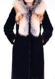 Schwarzer Schaffellpelzmantel mit dem Fuchskragen lokalisiert auf grauem Hintergrund Pelzmantel auf Modell ohne Gesicht oberbekle Lizenzfreie Stockbilder