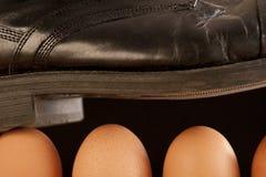 Schwarzer Schuh, der auf braune Eier geht Lizenzfreie Stockfotos