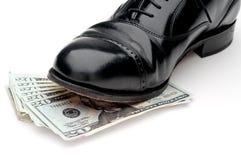 schwarzer Schuh, der auf einem Stapel des Geldes steht Stockbild