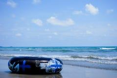 Schwarzer Schwimmring oder inneres Rohr auf sandigem Strand lizenzfreies stockbild