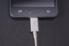 Schwarzer Smartphone auf schwarzem Hintergrund mit weißem Kabel Lizenzfreies Stockbild