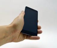 Schwarzer Smartphone in der Hand Lizenzfreie Stockbilder