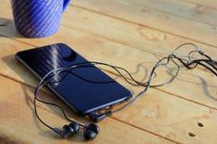 Schwarzer Smartphone und Kopfh?rer auf einem h?lzernen hellbraunen Hintergrund stockfoto