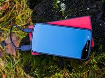 Schwarzer Smartphone und rotes powerbank Lizenzfreies Stockbild