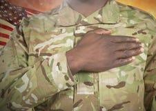 Schwarzer Soldat mit der rechten Hand gesetzt auf Herz für Unabhängigkeitstag Stockbilder