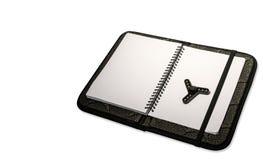 Schwarzer Spinner innerhalb des schwarzen Notizbuches lizenzfreie stockbilder