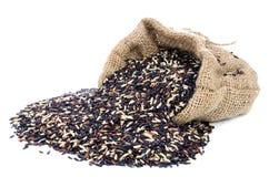 Schwarzer Stapel Reis in der Juteleinwandtasche mit weißem Isolathintergrund lizenzfreies stockfoto