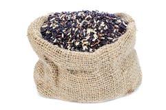 Schwarzer Stapel Reis in der Juteleinwandtasche mit weißem Isolathintergrund Lizenzfreies Stockbild