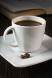 Schwarzer starker Kaffee auf dem Tisch und Lesebuch Lizenzfreie Stockfotos