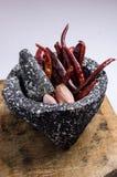 Schwarzer Steinmörser mit Bestandteilen für Soße, Pfeffer des roten Paprikas, rohe Knoblauchzehen stockbilder