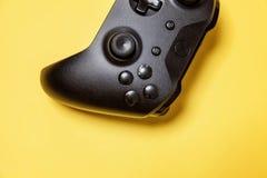 Schwarzer Steuerknüppel auf gelbem Hintergrund Computerspielwettbewerbsvideospielsteuerkonfrontationskonzept stockfotografie