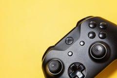 Schwarzer Steuerknüppel auf gelbem Hintergrund Computerspielwettbewerbsvideospielsteuerkonfrontationskonzept stockfoto