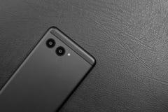 Schwarzer stilvoller Smartphone auf dunklem ledernem Hintergrund lizenzfreie stockbilder