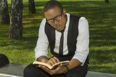 Schwarzer Student liest ein Buch Stockfotografie