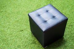 Schwarzer Stuhl auf Beschaffenheit des grünen Grases Stockfotografie