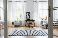 Schwarzer Stuhl am Schreibtisch im Kinderzimmer Innen mit Fenstern, Bett und Anlagen Reales Foto stockfoto