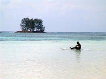 Schwarzer Surfer, der in den Ozean schwimmt und Ruder rudert Lizenzfreie Stockfotos