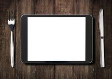 Schwarzer Tabletten-PC auf dunklem Holztisch mit Gabel und Lizenzfreies Stockbild