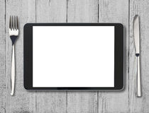 Schwarzer Tabletten-PC auf Holztisch mit Gabel und Lizenzfreies Stockbild