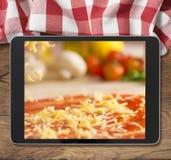 Schwarzer Tabletten-PC mit der Pizza angezeigt auf Holztisch- und Picknicktischdecke Lizenzfreie Stockbilder