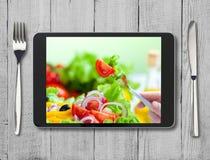 Schwarzer Tabletten-PC mit gesundem Lebensmittel auf Schirm und Holztisch Stockfoto