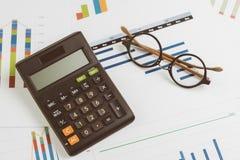 Schwarzer Taschenrechner, Brillen auf Monatsdiagramm und Diagramm auf Bürotisch mit als Firma Gewinn- und Verlust-, finanziell un lizenzfreies stockfoto