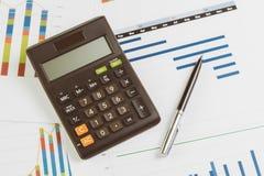 Schwarzer Taschenrechner, Stift auf Monatsdiagramm und Diagramm auf Bürotisch mit als Firma Gewinn- und Verlust-, finanziell und  lizenzfreies stockbild
