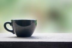 Schwarzer Tasse Kaffee auf Tabelle mit grünem Naturhintergrund Stockbild