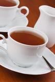 Schwarzer Tee in den Bechern mit Saucers Stockbilder