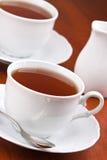 Schwarzer Tee in den Bechern mit Saucers Stockfoto