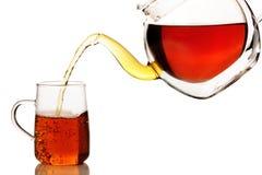 Schwarzer Tee, der in eine Schale ausgelaufen wird Stockbild