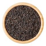 Schwarzer Tee in der hölzernen Schüssel lokalisiert auf weißem Hintergrund Lizenzfreie Stockbilder