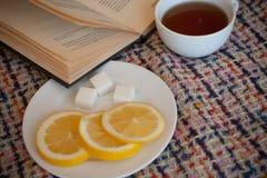 Schwarzer Tee des Morgens mit Zitrone und dem Ablesen eines Buches Lizenzfreies Stockfoto