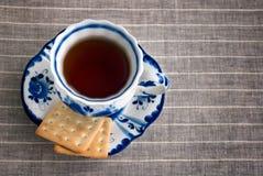 Schwarzer Tee diente in Porzellan Gzhel-Schale mit Crackern auf Untertasse Lizenzfreie Stockfotos