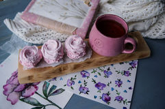 Schwarzer Tee in einer rosa Schale und in einem Nachtisch von einem rosa Zefir stockfotografie