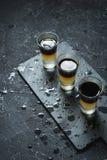Schwarzer tireur - schwarzer Balsam- und Pfirsichsaft Harte alkoholische Schüsse auf Steintabelle lizenzfreies stockfoto