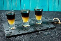 Schwarzer tireur - schwarzer Balsam- und Pfirsichsaft Harte alkoholische Schüsse auf Steintabelle stockfotografie