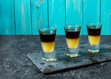 Schwarzer tireur - schwarzer Balsam- und Pfirsichsaft Harte alkoholische Schüsse auf Steintabelle lizenzfreie stockfotografie
