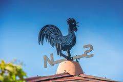Schwarzer und blauer Metallwetterhahn auf Dach mit dem blauen Himmel unfocused Lizenzfreie Stockfotografie