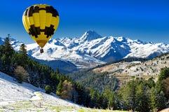 Schwarzer und gelber Heißluftballon mit Pic du Midi de Bigorre PY lizenzfreie stockbilder