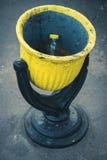 Schwarzer und gelber Stahlmülleimer auf der Straße stockbilder