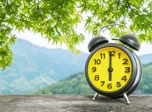 Schwarzer und gelber Wecker der Nahaufnahme für verzieren in 6 O-` Uhr auf unscharfen Blättern und Bergblickhintergrund Stockfotografie