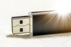 Schwarzer usb-Blitz-Antrieb auf weißem Hintergrund mit Sonnenstrahl Stockfoto