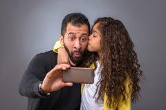 Schwarzer Vater, der selfies mit seiner Tochter nimmt Lizenzfreies Stockbild