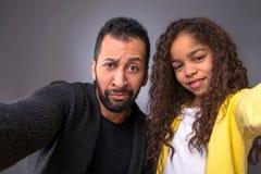 Schwarzer Vater, der selfies mit seiner Tochter nimmt Stockbild