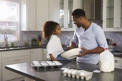 Schwarzer Vati und junge Tochter betrachten einander beim Backen Stockfotos