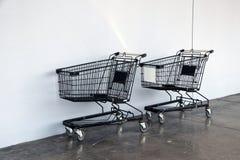 Schwarzer Warenkorb auf dem Boden und dem weißen Hintergrund Laufkatze ist ein Warenkorb, der durch einen Shop, besonders Supermä stockfoto